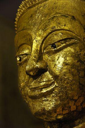 Buddha statue at Wat Bang Ko Theppasak, Amphawa Thailand covered with gold leaf placed by temple visitors wishing to make merit.