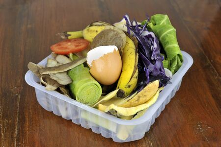 Kitchen vegetable and fruit food waste, collected in re-used packaging, for composting. Stock Photo