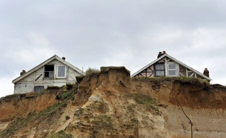the collapsing: Homes in danger on the cliff edge at Happisburgh in Norfolk demonstrating levels of erosion along the East Coast. UK.