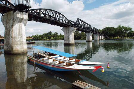 Thai longtail boats beside the River Kwai bridge, Kanchanaburi, Thailand. Editorial