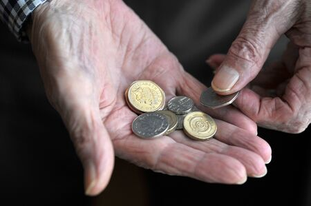 pensioner: Pensioner holding coins in the hand or counting cash, UK.