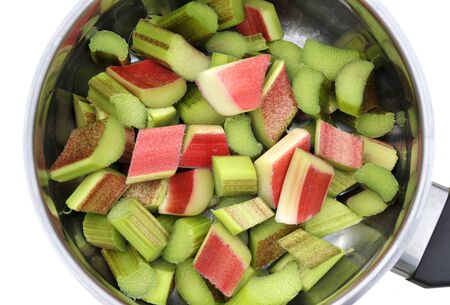 rheum: Rhubarb chopped ready to cook in a saucepan. Rhubarb is a herbaceous perennial vegetable which is often treated as a fruit in culinary use. Stock Photo
