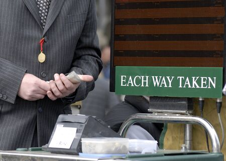 Racecourse bookmaker with cash in hand.