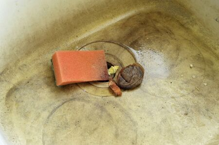 unhygienic: Stained and dirty unhygienic kitchen sink with wash sponge, food waste and used teabag.