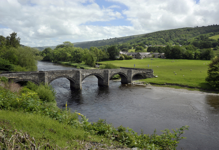 Stone bridge and River Dee in the village of Carrog, Dee Valley, Denbighshire, Wales, UK.