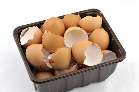 Egg shells kitchen food waste collected in a reused container for recycling via a home composter, wormery or in the garden.