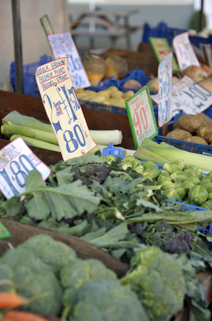 Greengrocer market trader vegetable stall with green brassicas, leeks, brussels sprouts, broccoli and purple sprouting broccoli.