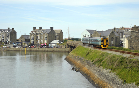 Barmouth town and harbour on the estuary of the river Mawddach and Cardigan Bay, the marina and quay with quayside railway line passing through the town in Gwynedd, North Wales, UK.