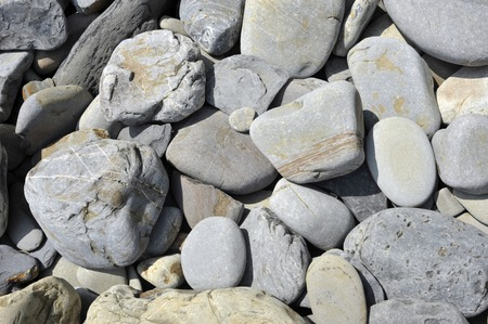 Grey stones or rocks on a beach in wales near Tenby, rounded and eroded by the action of the sea and weather. Stock Photo