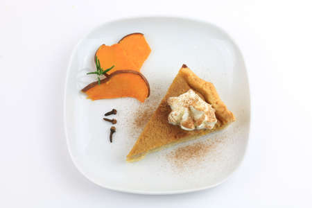 A slice of homemade sweet pumpkin pie isolated on white background. Top view Banco de Imagens