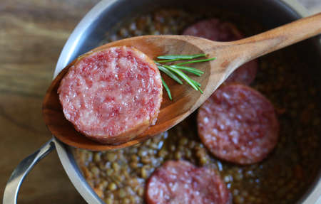 New Year's Eve Meal Italian Style. Top view of a slice of sausage (pork sausage) and rosemary on spoon. Background with pot with lentils.