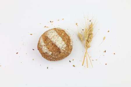 Wholemeal bread with wheat ears isolated on a white background