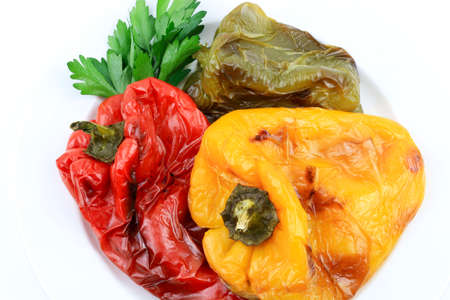 Various color roasted peppers on white background