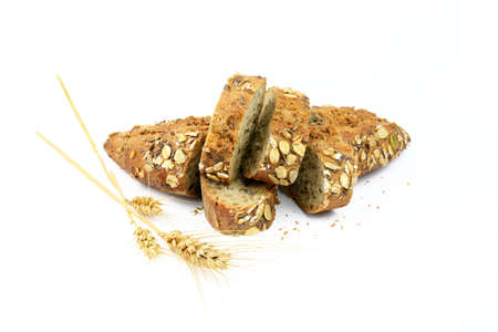 Slices of wholemeal bread with ears of wheat on a white background