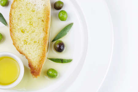 Fresh olives, olive oil and bread on white background
