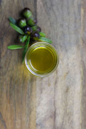 Fresh olives and olive oil on wooden table
