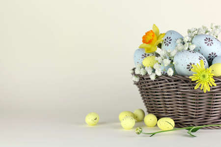 Easter eggs and flowers in basket isolated Stock Photo - 131786715