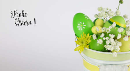 Easter eggs and flowers in basket with tag Foto de archivo