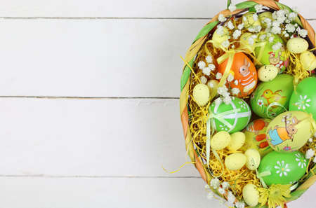 Easter eggs and flowers in basket isolated Foto de archivo