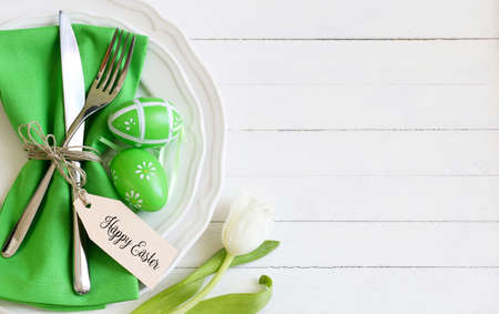 Easter table with cutlery on wooden table with tag Foto de archivo