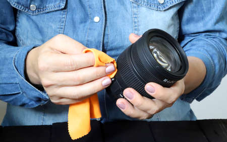 Closeup of woman hands cleaning camera lens
