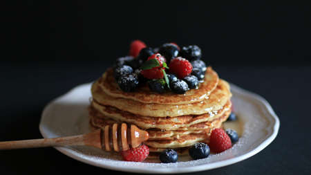 Stack of pancakes with honey, blueberries and red raspberries with icing sugar on a dark background 版權商用圖片
