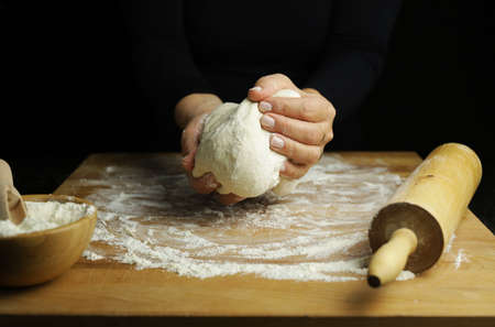 Preparing traditional homemade dough. Close up view of woman hands making fresh bread for pizza on a floured table Stok Fotoğraf