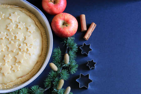 Homemade american traditional holiday pie. Apple pie unbaked decorated with stars, cinnamon, red apple, star anise, lights and fir branch in dark back