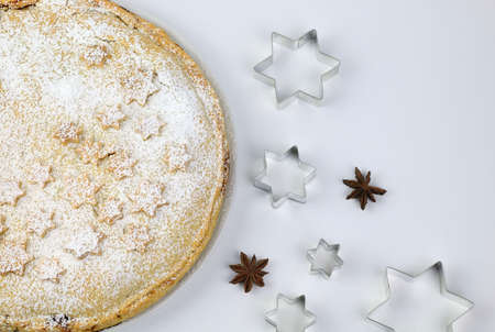Homemade american traditional holiday pie. Apple pie dessert decorated with stars, cinnamon, red apple, star anise in white background. Top view Stok Fotoğraf