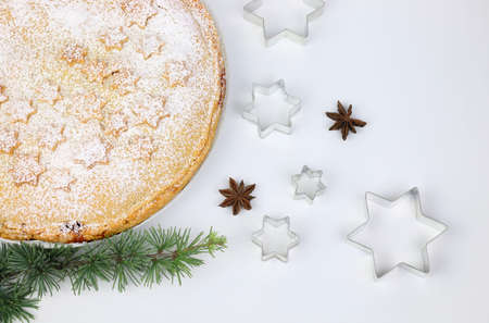 Homemade american traditional holiday pie. Apple pie dessert decorated with stars, cinnamon, red apple, star anise and fir branch on white background. Stok Fotoğraf