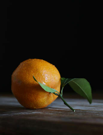 Close up of single fresh mandarin with leaf on wooden table Stok Fotoğraf