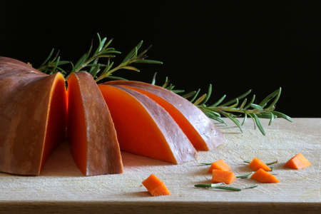 Closeup of a pumpkin with rosemary on a wooden table. Raw vegetables