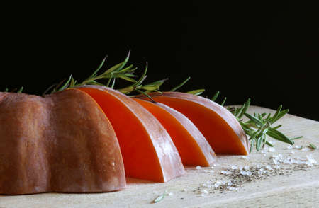 Closeup of a pumpkin with rosemary on wooden table. Raw vegetables