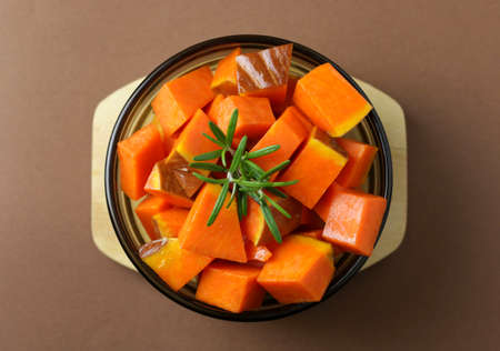 Top view of pumpkin with rosemary in a round glass plate on dark background. Raw vegetables.