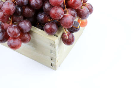 Ripe red grapes in a wooden box isolated on white background