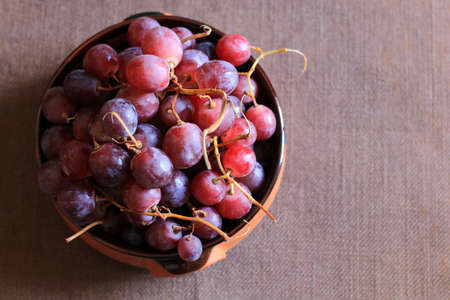Ripe red grapes in a bowl isolated on brown background Stok Fotoğraf