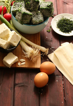 Traditional greek cuisine. Top view of ingredients for Spanakopita pie with spinach and feta cheese on wooden table.
