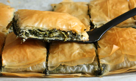 Traditional greek cuisine. Spanakopita pie with spinach and feta cheese on dark background