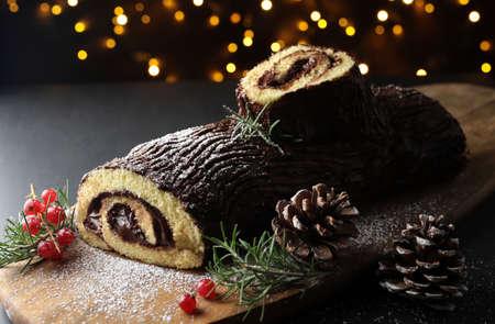 Chocolate Christmas Yule Log, Buche de Noel on wooden cutting board. Christmas decoration on dark background. Closeup Stok Fotoğraf