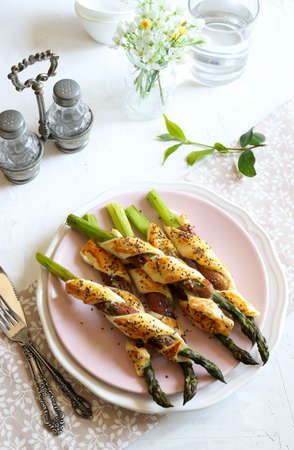Top view of roasted asparagus rolls with prosciutto and puff pastry on a table. Menu concept. Standard-Bild