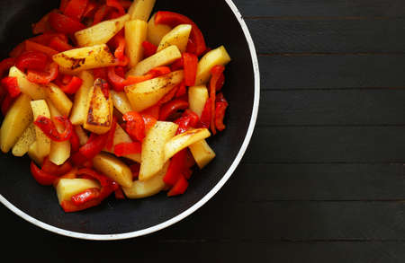 Homemade food concept. Potatoes and peppers side dish in a pan. Dark wooden background.Top view.