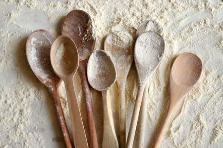 Baking concept. Top view of wooden spoons sprinkled with wheat flour on flour background.