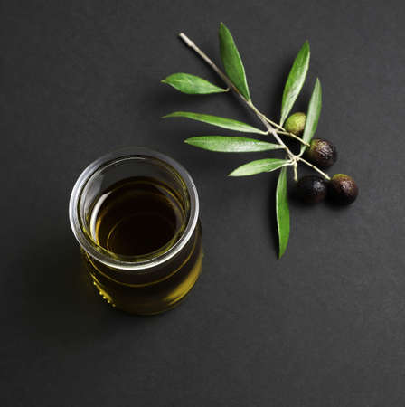 Glass bowl of fresh extra virgin olive oil and green olives with leaves isolated on dark background Stockfoto