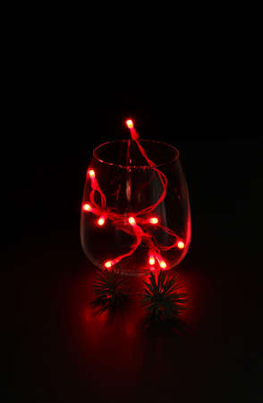 Concept of Christmas. Glass with red lights on dark background. Christmas decorations.