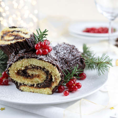 Traditional Christmas dessert. Buche de Noel. Christmas yule log cake with chocolate cream and currant.