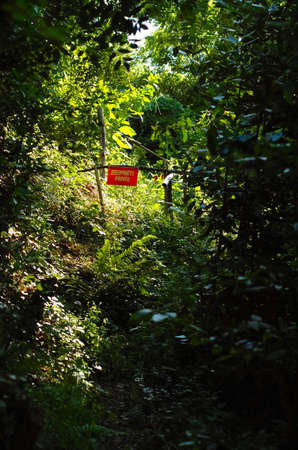Path in an undergrowth on a barrier with a sign of private ownership