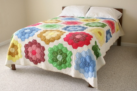 red pillows: Bed with floral quilt Stock Photo