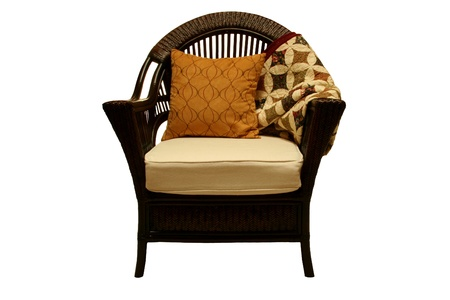 Wicker chair with quilt and pillow Stock Photo