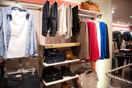ropa colgada: Los estantes y perchas en la tienda de ropa Editorial