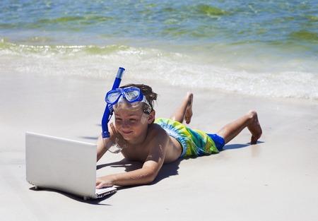 Smiling little boy using laptop lying on beach Stock Photo